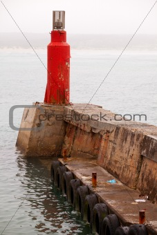 Bright red lighthouse on pier in harbor