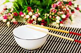 Chopsticks and bowl on the bamboo mat