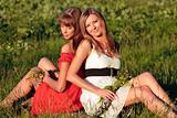 Two beautiful caucasian girls sitting on a meadow