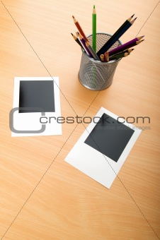 Blank instant photos and pencils on the wooden table
