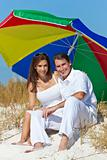 Man & Woman Couple Under Multi Colored Umbrella on Beach