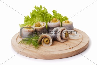 A composition with marinated herring rolls