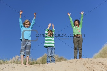 Three Children Arms Raised Having Fun on Beach