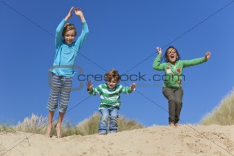 Three Children Arms Raised Jumping Having Fun on Beach
