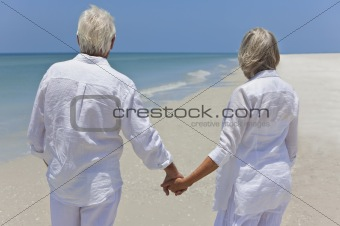 Senior Couple Holding Hands &amp; Looking To Sea on Beach