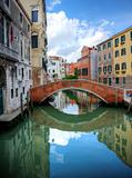 Beautiful reflections of bridge in canal in Venice Italy