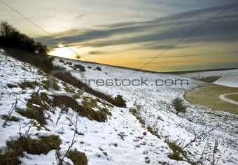 Beautiful Winter landscape over fields with glowing sunset