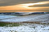 Winter snow landscape over fields with trees and glowing sunset