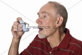 Old man using asthma inhaler