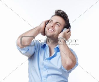 man in blue shirt with earphones listening to music - isolated on gray