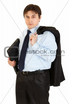 Thoughtful young businessman with jacket on his shoulder holding folder in  hand