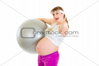 Smiling beautiful pregnant woman holding fitness ball and showing thumbs up gesture