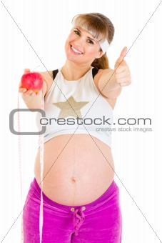 Smiling beautiful pregnant woman with measure tape and apple showing thumbs up gesture