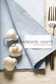 fork and mushrooms on blue napkin