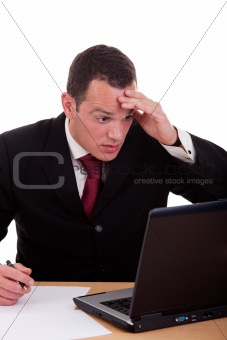 businessman  surprised and worried looking to computer, isolated on white background. Studio shot.
