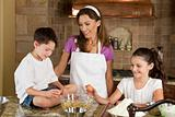 Mother, Son &amp; Daughter Family In Kitchen Cooking Baking 