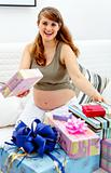 Happy  beautiful pregnant female sitting on sofa with gifts for her unborn baby