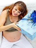 Smiling  beautiful pregnant woman sitting on couch with gift for her  unborn baby
