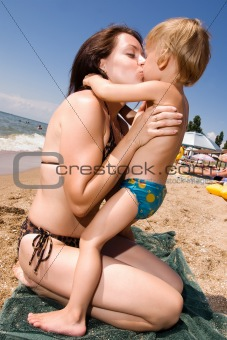Young mother kissing her son at the beach