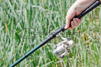Fisherwoman hand holding a fishing rod