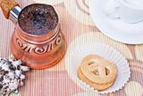 Turkish coffee in copper coffee pot with cookies