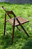 Wooden camp chair on green grass