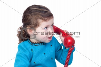 Beautiful baby girl with a red telephone