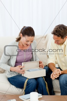 Amazed woman opening a present from his boyfriend on the sofa