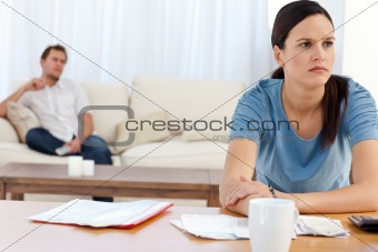 Angry woman doing her account while her boyfriend relaxing