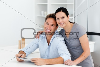 Portrait of a couple doing crossword together in the kitchen