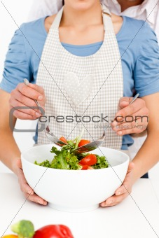 Close up of a couple mixing a salad together in t