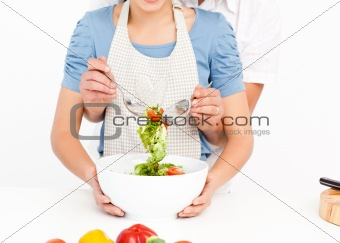 Close up of a man mixing a salad with his girlfriend