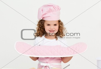 Little girl wearing kitchen gloves standing in the kitchen