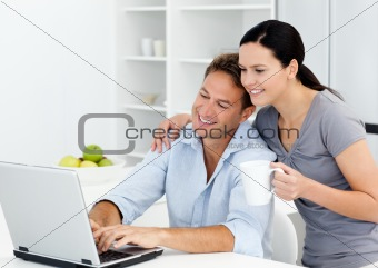 Affectionate woman looking at her boyfriend working on the laptop