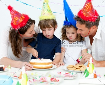 Cute little boy cutting a birthday cake for his family