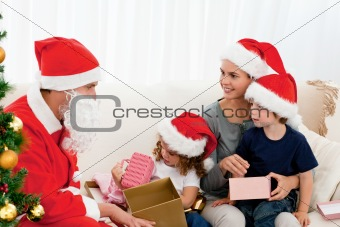 Santa giving presents to his children in the living room