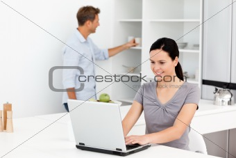 Cute woman working on the laptop in the kitchen