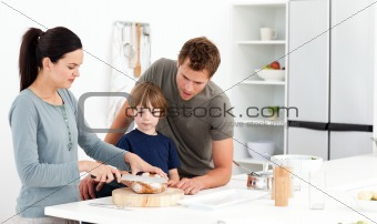 Lovely woman cutting bread for her son ad husband