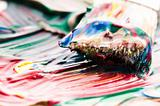 Brush mixing paint on palette