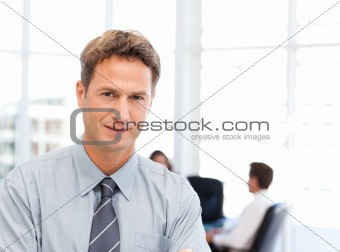 Severe businessman standing in front of his team while working 