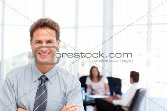 Proud businessman posing in front of his team while working