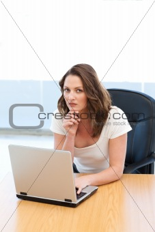 Attractive businesswoman working on laptop at a table