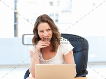 Happy businesswoman working on laptop at a table