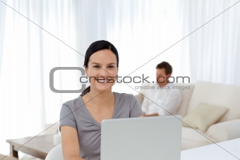 Cute woman working on the laptop while her husband relaxing