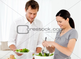 Happy woman serving salad to his boyfriend for the lunch