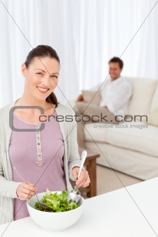 Pretty woman preparing a salad in the kitchen for her boyfriend