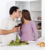 Cute couple kissing while having lunch in the kitchen