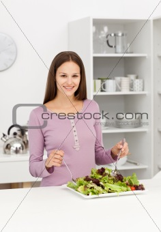 Cute woman mixing a salad standing in the kitchen
