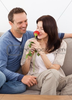 Cute woman smelling a red rose while relaxing on the sofa