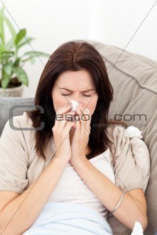 Portrait of a sick woman blowing her nose on the sofa